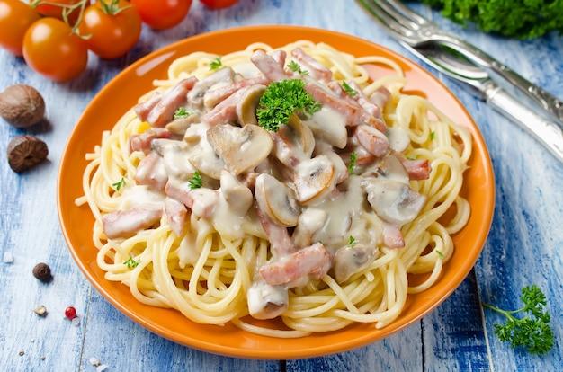 Спагетти с грибами соусом бешамель и беконом на деревянном столе