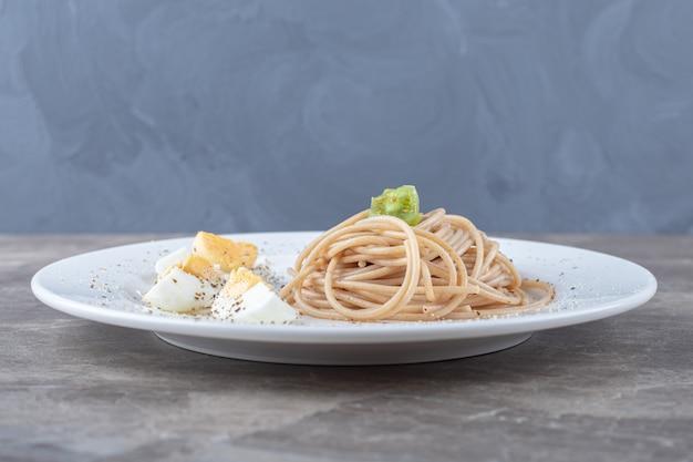 Спагетти с вареным яйцом на белой тарелке.