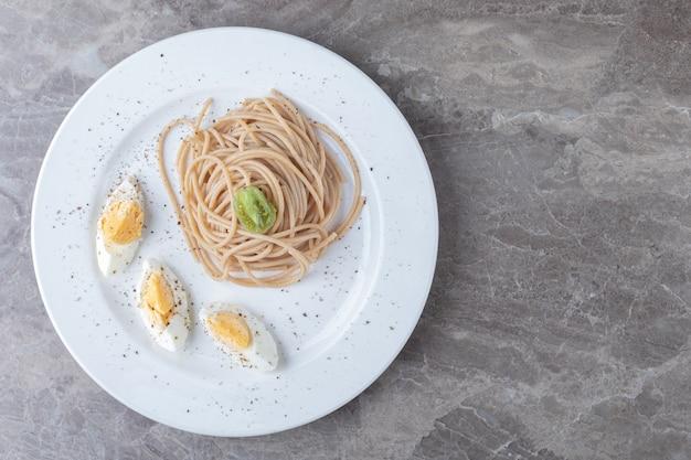 Spaghetti con uovo sodo sul piatto bianco.