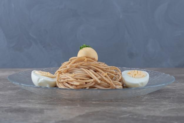 Спагетти с вареными яйцами на стеклянной тарелке.