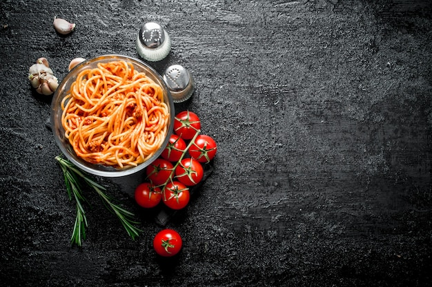 Spaghetti with bolognese sauce in a glass bowl with tomatoes,rosemary and garlic. on rustic