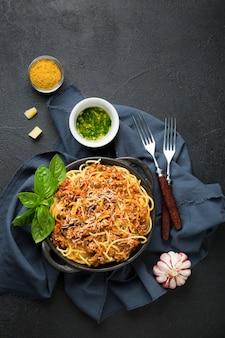 Спагетти с соусом болоньезе, оливками и специями на черной поверхности