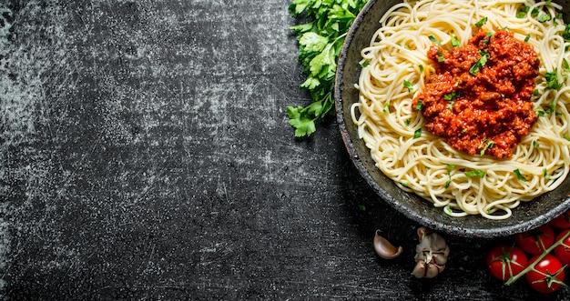 Спагетти с соусом болоньезе. на черном деревенском фоне
