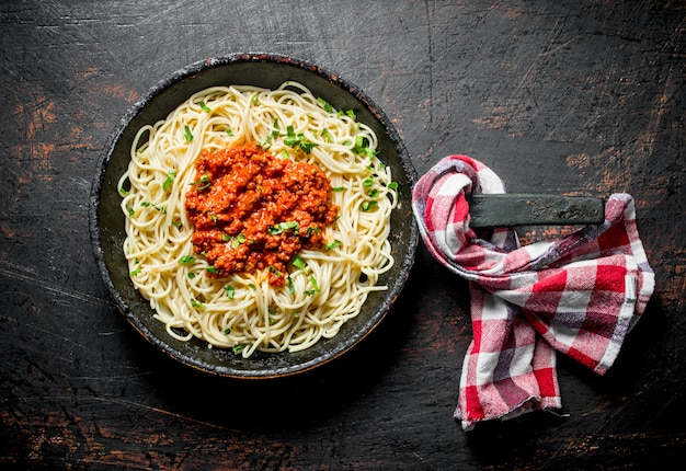 Spaghetti with bolognese sauce in pan with napkin. on dark rustic background