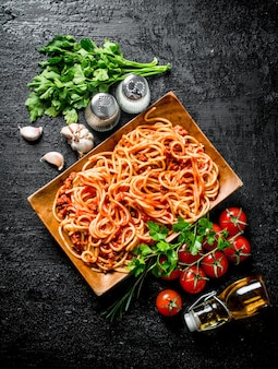 Spaghetti with bolognese sauce on a plate with herbs, tomatoes and garlic. on rustic surface