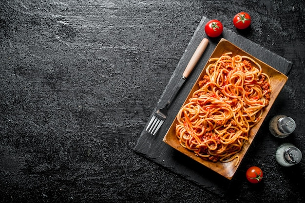 Spaghetti with bolognese sauce on a plate with spices and tomatoes. on rustic