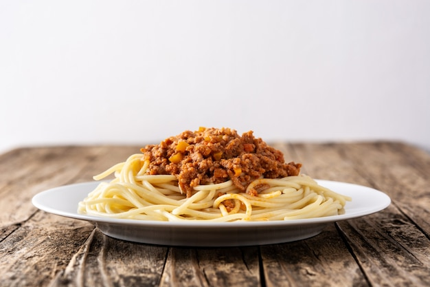 Spaghetti with bolognese sauce on wooden table