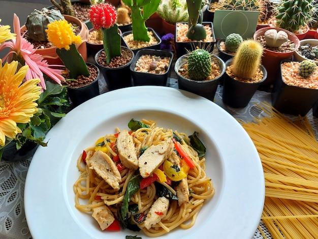 白いプレートとサボテンと多肉植物の背景に鶏の胸肉と唐辛子のスパゲッティ