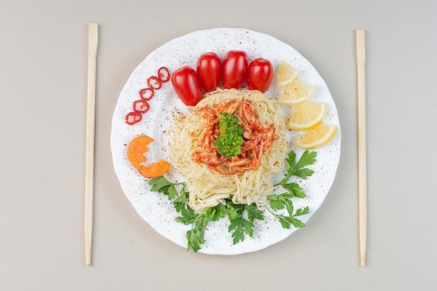 Спагетти с нарезанной курицей и овощами на белой тарелке