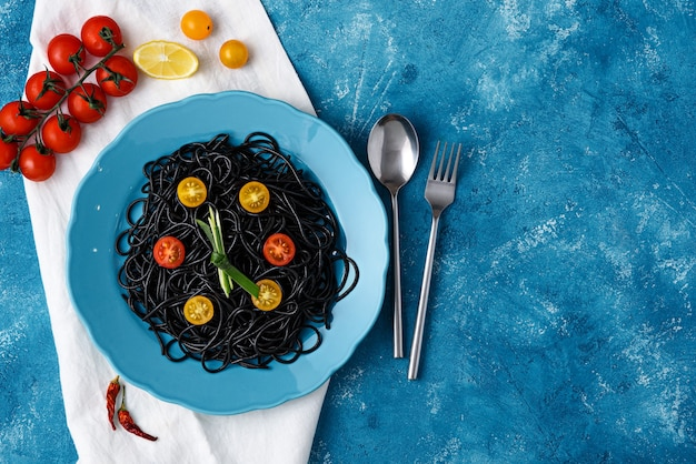 Spaghetti with cuttlefish ink with yellow and red cherry tomatoes on blue plate on blue background with copy space