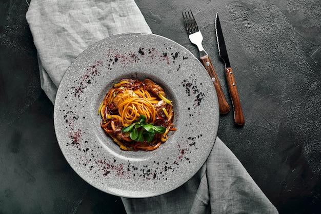 アヒルと野菜のスパゲッティイタリア料理グレープレートとダークフードのパスタの美しいサービング食べ物の写真、広告バナー、