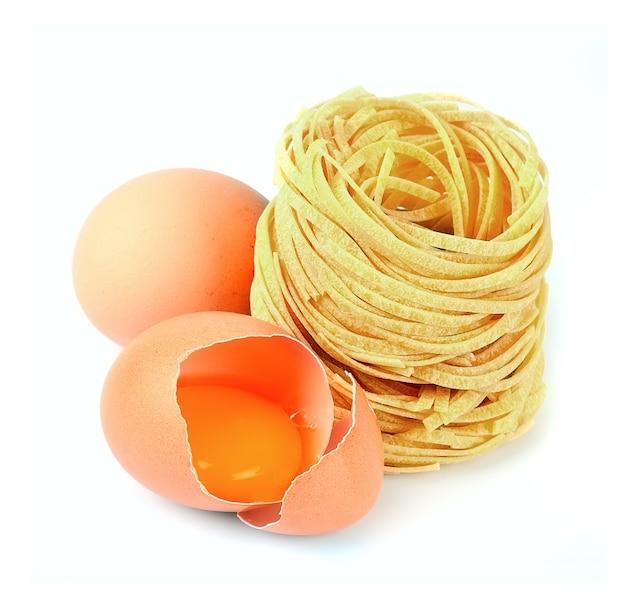 白い背景の上の卵とスパゲッティ。