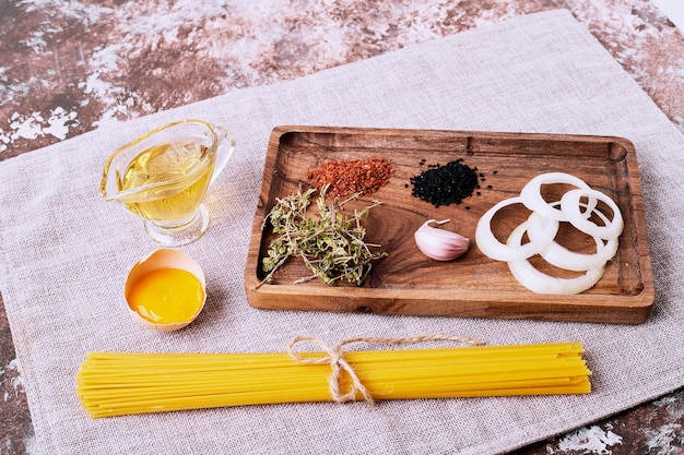 Spaghetti with fresh herbs on brown table.