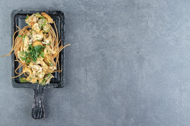 Spaghetti with fried egg on black board