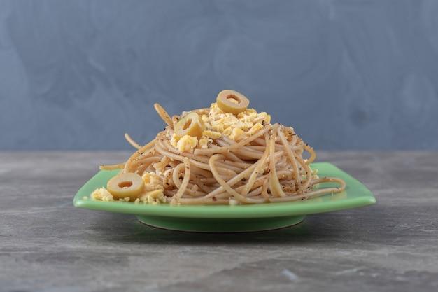 Spaghetti con uova fritte sul piatto verde.