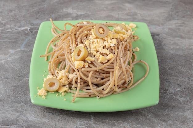 Спагетти с яичницей на зеленой тарелке.