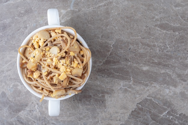 Spaghetti with fried eggs in white mug.