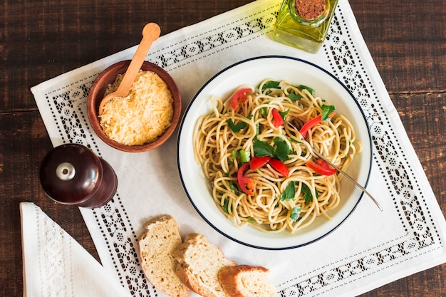 Spaghetti with grated cheese; bread and olive oil on white place mat