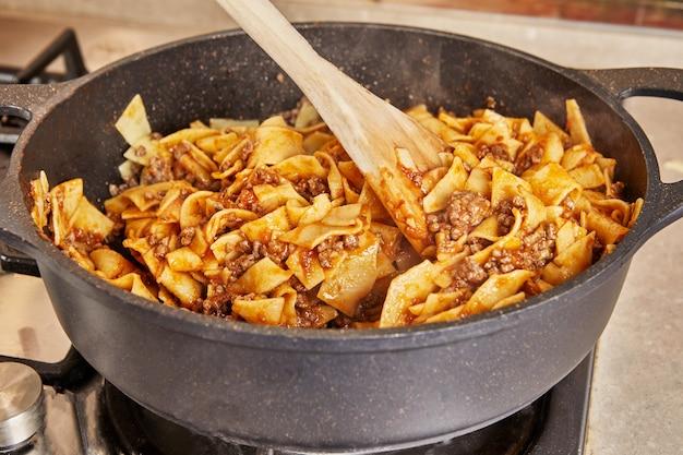 インターネットからのレシピに従ってスパゲッティボロネーゼを作るために鍋で揚げた牛ひき肉とソースのスパゲッティ