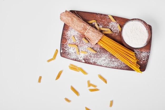 Spaghetti con ingredienti su bianco.