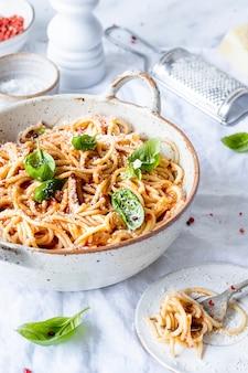 パルメザンチーズとバジルのフードフォトグラフィーをトッピングしたマリナーラトマトソースのスパゲッティ