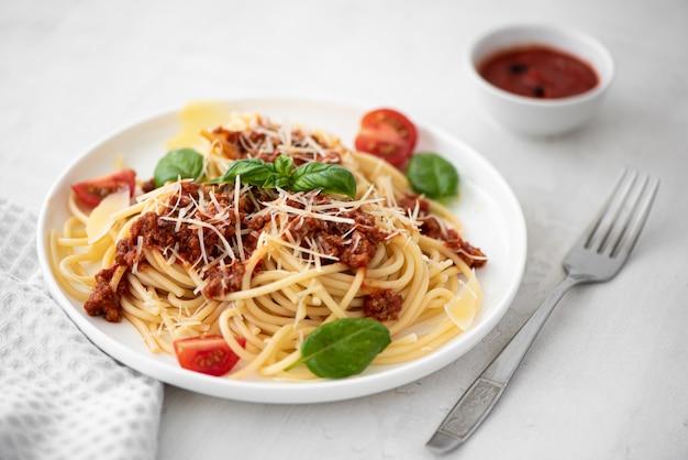 白い皿にミートソース、パルメザンチーズ、バジルのスパゲッティ
