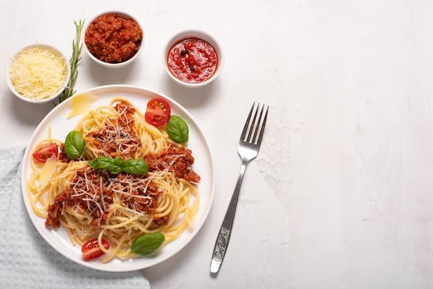 Спагетти с мясным соусом, пармезаном и базиликом на белой тарелке