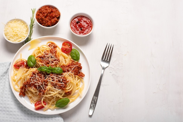 Spaghetti with meat sauce, parmesan and basil on a white plate