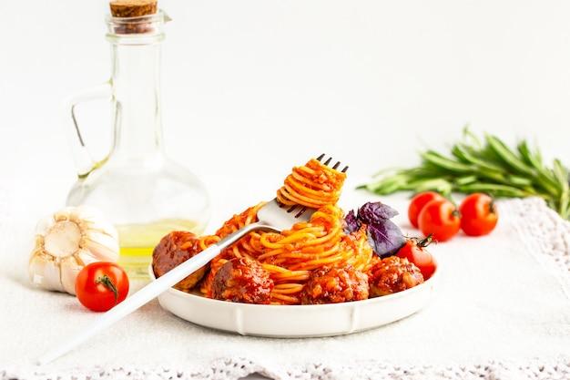 ミートボール、トマトソース、バジルのスパゲッティ。スパゲッティとバジルのフォークのミートボール。イタリアのパスタ。トマトソースのミートボール。ボリュームたっぷりの美味しいディナー。晩ごはん。イタリア人の好きな食べ物。