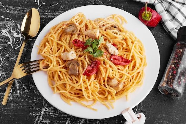 Спагетти со смешанными ингредиентами в белой тарелке с отставленными столовыми приборами.