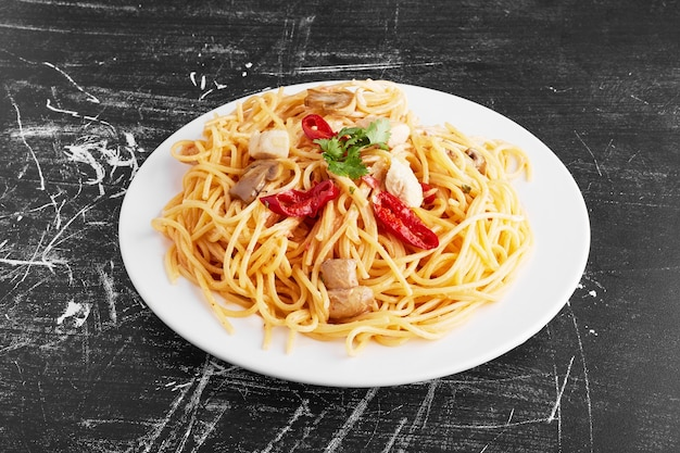 Spaghetti with mixed ingredients in a white plate on black background, top view.