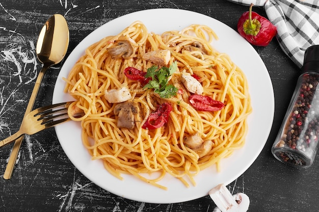 Spaghetti with mixed ingredients in a white plate with cutlery set aside.