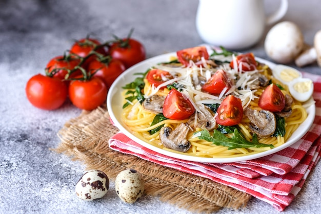 キノコ、チーズ、ほうれん草、ルッコラ、チェリートマトのスパゲッティ。イタリア料理、地中海文化