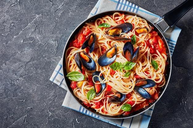 スパイシーなトマトソースのムール貝とコンクリートのテーブルのフライパンのスパゲッティ、上からの水平方向のビュー、フラットレイ、空きスペース