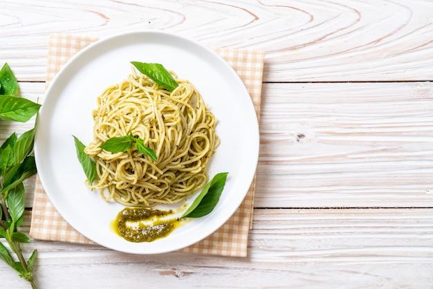 Spaghetti with pesto sauce, olive oil and basil leaves.