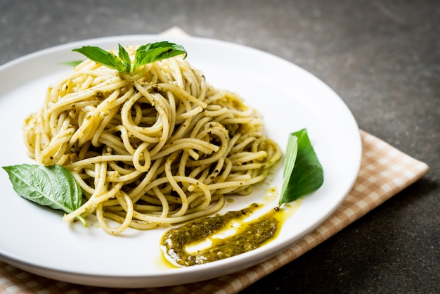 Spaghetti with pesto sauce, olive oil and basil leaves.