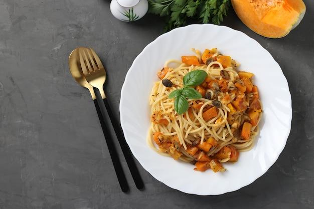 Спагетти с тыквой и тыквенными семечками в белой тарелке на темно-сером фоне.