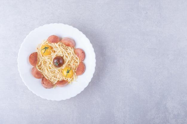 Спагетти с жареными сосисками и помидорами в белой миске.
