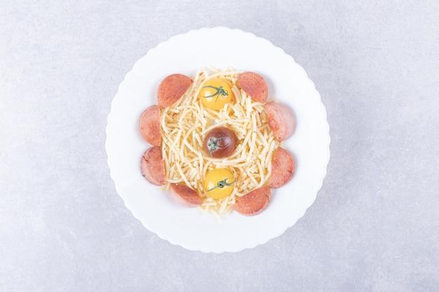 Spaghetti con salsicce arrosto e pomodori in una ciotola bianca.