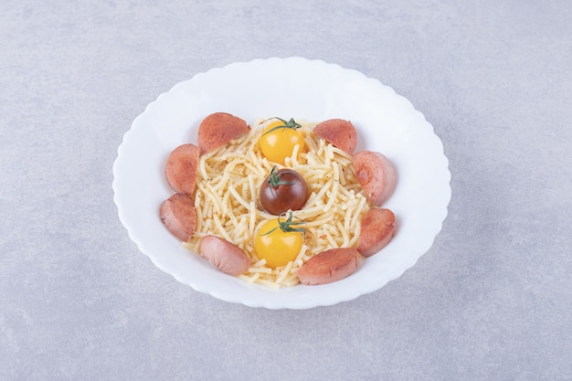 Spaghetti with roasted sausages and tomatoes in white bowl.