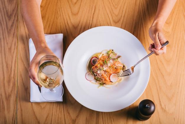 Спагетти с лососем девушка ест с бокалом белого вина. вид сверху