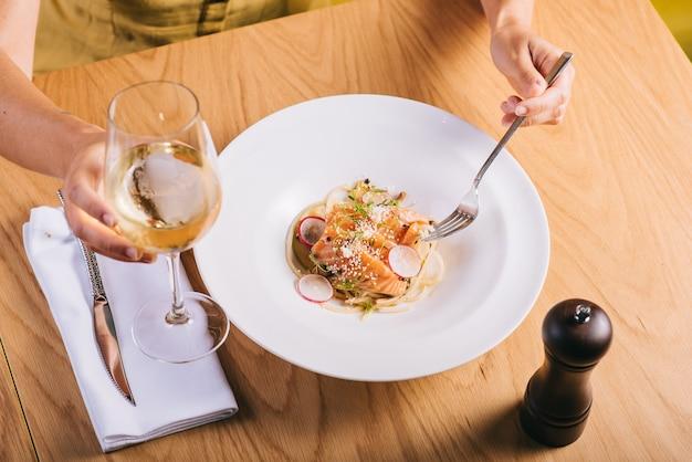 Спагетти с лососем девушка ест с бокалом белого вина