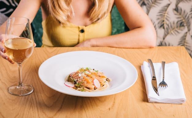 Спагетти с лососем на фоне девушка с бокалом белого вина