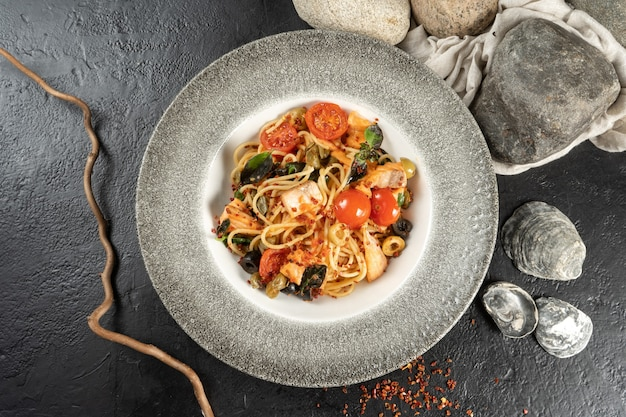 Spaghetti with salmon and vegetables. a hot main course of pasta, sea fish, tomatoes, capers, olives and olives