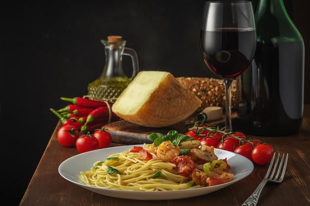 木製の背景にエビ、チェリートマト、スパイスのスパゲッティ。
