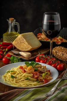 Spaghetti with shrimps, cherry tomatoes and spices on wooden background. food background.