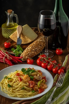 Spaghetti with shrimps, cherry tomatoes and spices on wooden background