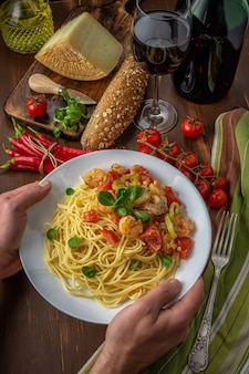 Spaghetti with shrimps, cherry tomatoes and spices on wooden background.