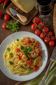 Spaghetti with shrimps, cherry tomatoes and spices on wooden.