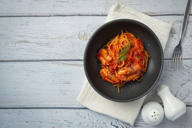 白い木製の背景にトマトソースのエビとスパゲッティ